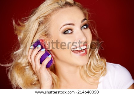 Vivacious blond woman brushing her hair as she looks sideways at the camera with a playful laugh - stock photo