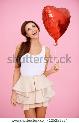 Vivacious brunette woman ina sexy miniskirt with a red heart shaped Valentine balloon in her hand on a pink studio background - stock photo