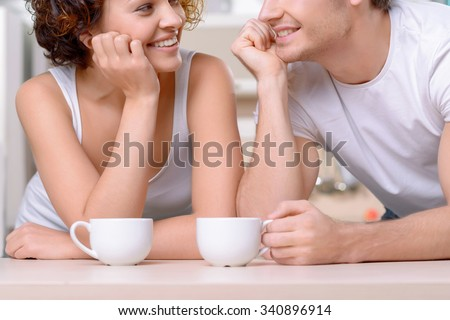 Vivacious conversation. Close up of cheerful delighted young couple looking at each other and leaning on the table while drinking coffee - stock photo