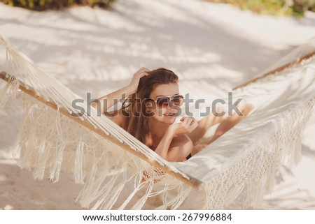 Vivacious happy woman laying elegantly on a hammock in a bikini. Woman relaxing on hammock sunbathing on vacation.