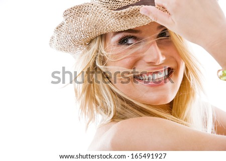 Vivacious healthy beautiful blond woman with a lovely playful smile and windblown long blond hair holding onto a trendy straw hat as she looks back over her shoulder, on white
