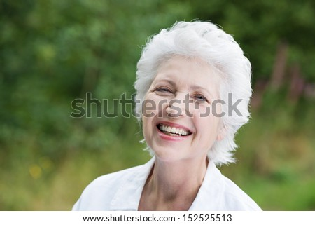 Vivacious laughing grey haired senior woman outdoors in a lush green park, close up portrait