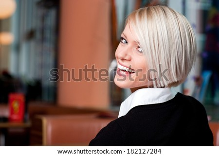 Vivacious laughing young blond woman in a restaurant looking back over her shoulder at the camera with a beaming smile - stock photo