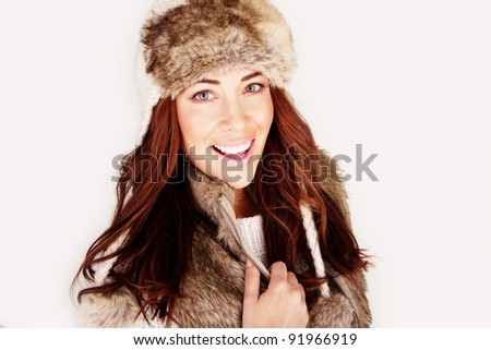 Vivacious redhead woman in winter outfit wearing fur hat and jacket, close-up head and shoulders, studio on white - stock photo