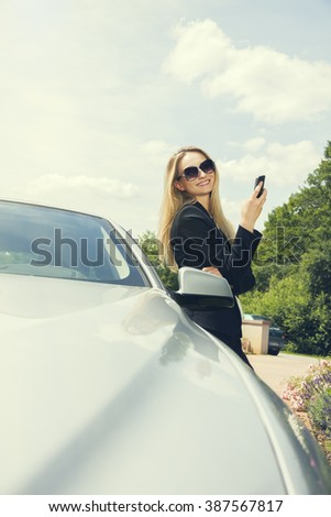 Vivacious stylish young blond woman chatting on a mobile phone as she leans back against a car