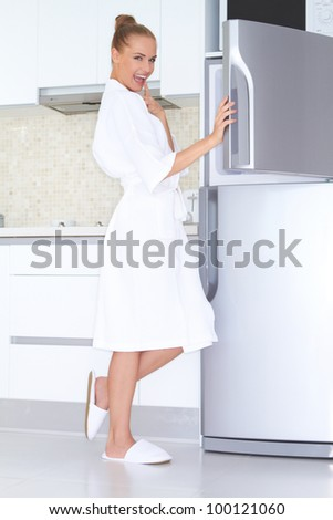 Vivacious woman in a white bathrobe and slippers standing laughing as she opens the freezer unit of her refrigerator - stock photo