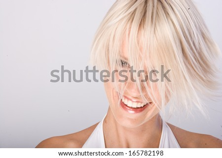Vivacious young woman with a trendy blond hairstyle flicking her short hair in the air as she laughs at the camera - stock photo