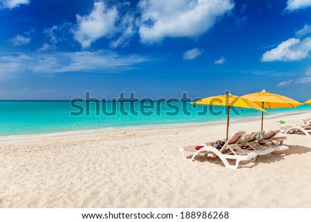 Vivid blues and turquoise with white sands, Grace Bay Beach, Turks & Caicos. Bright yellow beach umbrellas make a great contrast color - stock photo