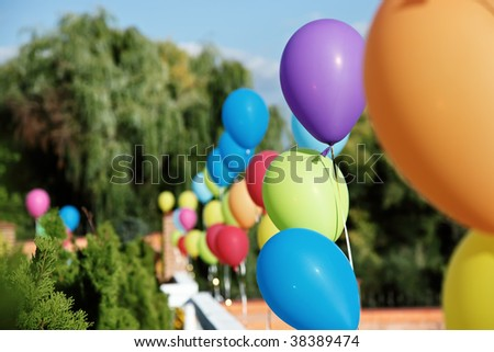 Vivid color balloons on green outdoor background - stock photo
