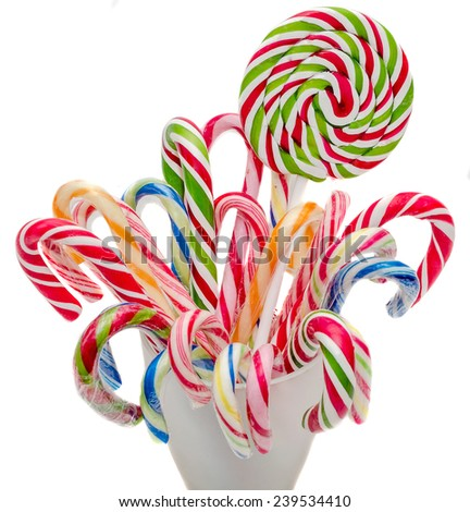 Vivid colored candy christmas sticks, lollipops in a transparent vase, spiral shape, round,  isolated, white background. - stock photo