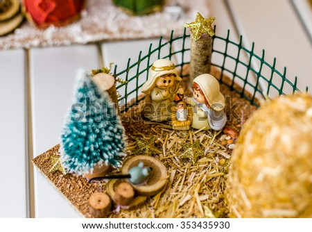 vivid colors of a Christmas Nativity scene, the Blessed Virgin Mary and Saint Joseph watch over the Holy Child Jesus in a manger - stock photo
