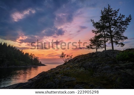 vivid colors of sunset over rocky lake shores