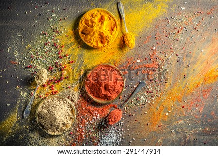 Vivid condiments on old table - stock photo