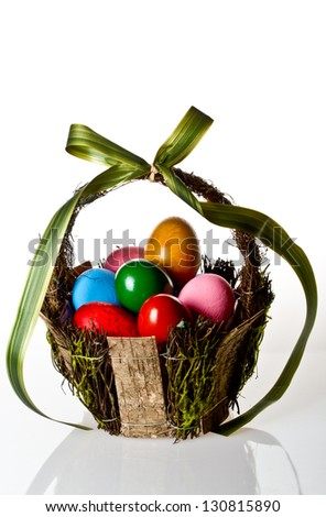 Vivid Easter egg basket on white background - stock photo