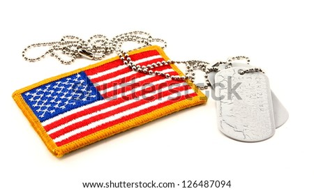 Vivid embroidered American Flag patch and vintage dog tags - stock photo
