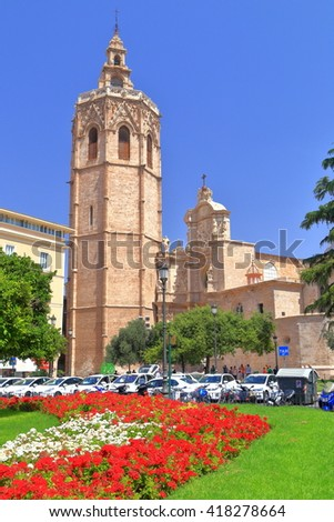 Vivid flowers and distant Miguelete tower near the Metropolitan Cathedral - Basilica of the Assumption of Our Lady of Valencia (known as Saint Mary's Cathedral or Valencia Cathedral), Valencia, Spain - stock photo