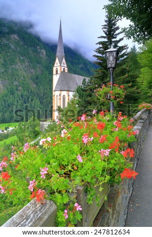 Vivid flowers on a street in Heiligenblut and distant tower of St Vincent church in cloudy day, Austria - stock photo