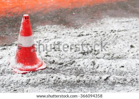 Vivid orange traffic cone on the snowy road  - stock photo