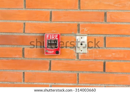 Vivid red fire alarm pull station on the old brick wall