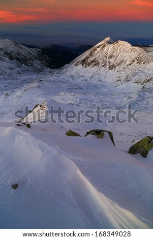 Vivid sky and snow covered mountains after sunset - stock photo