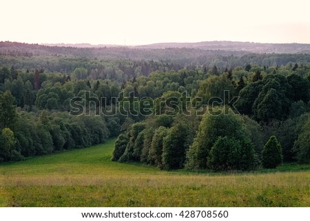 Vivid summer forest between hills scene toned by beautiful sunset in Russia. Fresh panoramic sunset forest view. Deep green forest at sunset. Sunset forest view. Scenic summer forest view from a hill. - stock photo