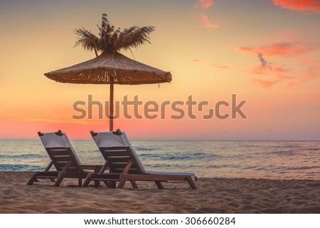 Vivid sunrise on a beautiful sandy beach with sunshade  - stock photo