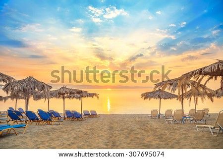 Vivid sunrise on a beautiful sandy beach with sunshade - stock photo