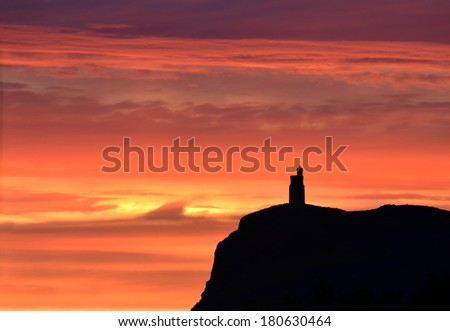 Vivid Sunset colours with silhouette of Milner Tower on Brada Head, Isle of Man, UK