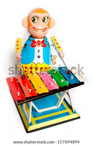 vivid tin toy  wind up monkey musician retouched and isolated on white background - stock photo
