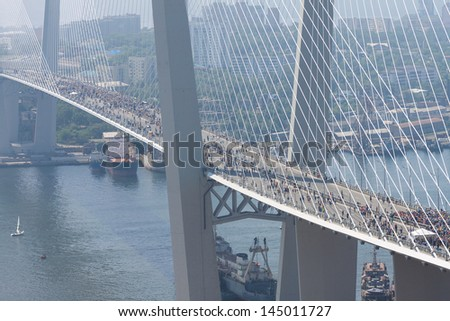 "VLADIVOSTOK, RUSSIA - JULY 7: Flashmob ""I love Vladivostok"" on the ""Golden Bridge"". 26,904 people who have created a ""live"" 707-meter Russian flag on July 7, 2013 in Vladivostok, Russia."