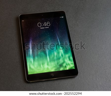 VLADIVOSTOK, RUSSIA - JUNE 4, 2014: Apple iPad mini displaying iOS 7 screen saver screen, russian version. iOS 7 operating system designed by Apple Inc.  - stock photo