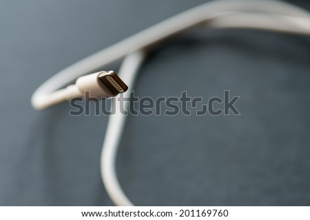 VLADIVOSTOK, RUSSIA - JUNE 4, 2014: Apple Lightning Connector on dark background. Is a proprietary connector used to connect mobile devices  such as iPhones, iPads or iPods to computers.   - stock photo