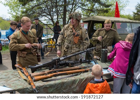 VLADIVOSTOK, RUSSIA - MAY 9, 2014: Children inspect weapons since World War II during festivities devoted to Victory Day.
