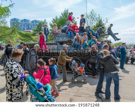 VLADIVOSTOK, RUSSIA - MAY 9, 2014: Children play on restored T-34 medium tank during festivities devoted to Victory Day.