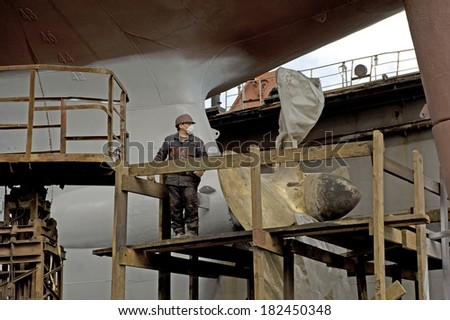 "Vladivostok, 26.05.2010  Unidentified men, the brigade painters paint the hull in dry dock ""Dalzavod""       city  of  Vladivostok  - stock photo"