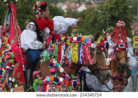 VLCNOV, CZECH REPUBLIC - MAY 26, 2013: Young men dressed in Moravian folk costume ride decorated horses during the Ride of the Kings folklore festival in Vlcnov, South Moravia, Czech Republic.