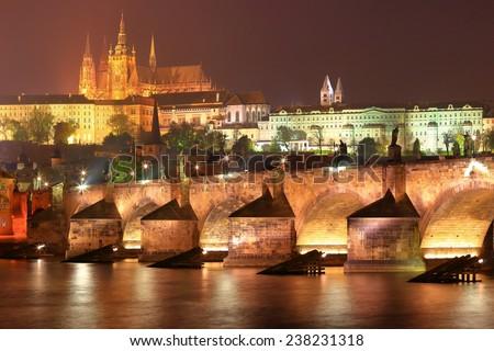 Vltava river flowing under the Charles bridge and distant Prague Castle illuminated by night, Prague, Czech Republic - stock photo