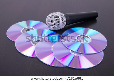 Vocal microphone and cd discs on table, closeup - stock photo