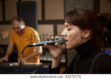 vocalist girl is singing in studio. keyboard player in out of focus - stock photo