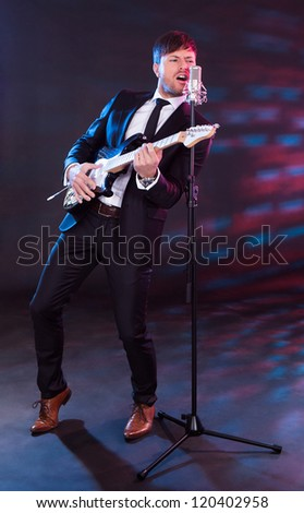 Vocalist sings with guitar while leaning back and pointing toe. - stock photo