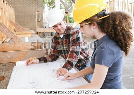 Vocational education student learning to read construction blueprints.   - stock photo