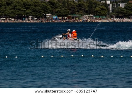 Vodice, Croatia, July 4, 2017 two people riding on sea scooter