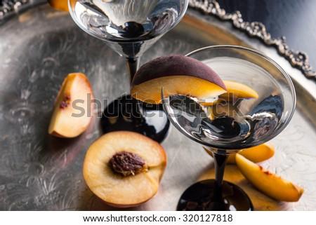 Vodka and martini with fresh peaches - stock photo