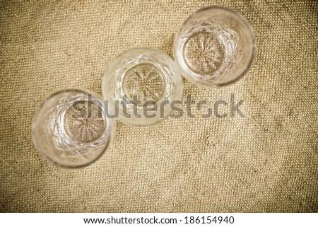 Vodka glasses on retro linen fabric texture. - stock photo