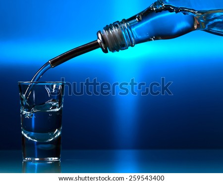 vodka in bar on a glass table, focus on glass - stock photo