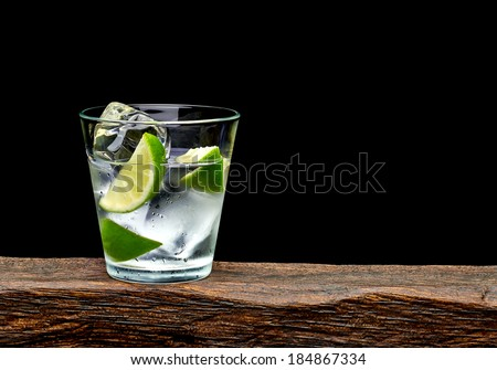 Vodka, lime wedge with ice in rocks glass on log with black background - stock photo