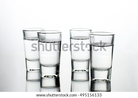 Vodka shots filled with alcohol on glass bar table