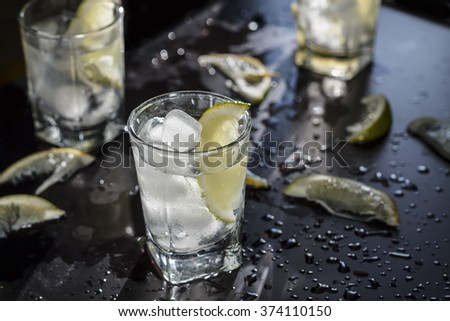 Vodka, vodka, tequila, gin in a glass with ice on black table, closeup