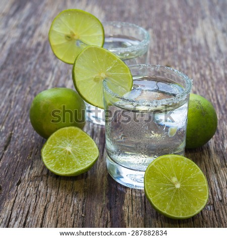 Vodka with lemon on wooden table, rustic style - stock photo
