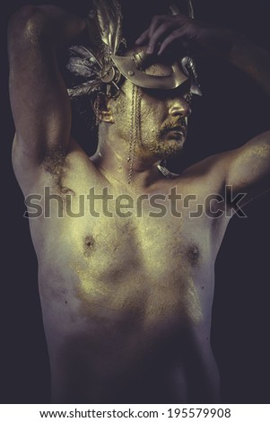 Vogue Man with body painted gold feather mask and steel sword - stock photo